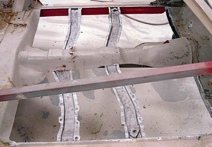 The floorpans are a major structural component of the body, and therefore when cut¬ting out the floors, the body can move out of alignment. You don't want to install the floorpans when the body isn't square. Hence, you need to install these brace bars and take the proper measurements to ensure that the body is square. This is not really necessary for a floorpan replacement, but if your car is also getting quarter panels it needs the support. These floor braces have been soda blasted and primed. Once the floor braces are stripped, the pans are ready for installation. (Photo Courtesy Scott Tiemann)