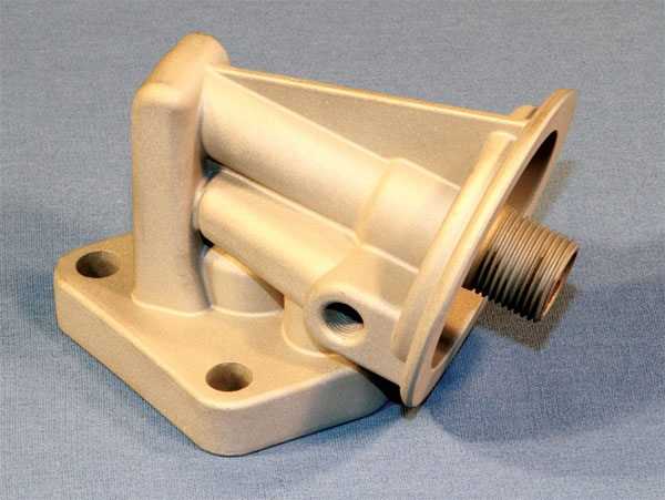APE and KRE reproduce Pontiac oil filter housing. The unit from APE includes a stock-type bypass while the unit from KRE is left as cast, and not functional. Both are distributed by many companies for less than $75.