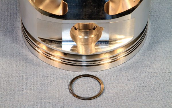 Lock rings are used to retain floating wrist pins, and two are generally used on each end. The rings are coiled much like a key ring, and proper installation consists of gently stretching the lock ring to separate the coils and then placing the lock ring in the corresponding groove that is machined into the piston and gradually walking it around until it snaps into place. New lock rings should be used during each teardown.