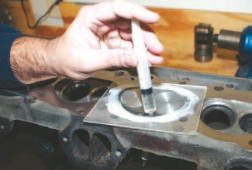 Measuring combustion chamber volume is an accurate way to determine compression ratio. Most shops have precision equipment available, but I have found that I can replicate those results by using graduated syringes sourced from an animal feed supply store, a thick piece of clear plastic with two holes drilled into it, and rubbing alcohol. I mount a cylinder head onto a cylinder head stand, level it out, apply a thin coat of white grease around the chamber, lay the plastic piece in place, and then insert a measured amount of fluid into the chamber through one hole while trapped air bleeds out of the other. I carefully record the amount of volume the chamber displaces. These 670 castings measured exactly 75 cc after the chambers were relieved.