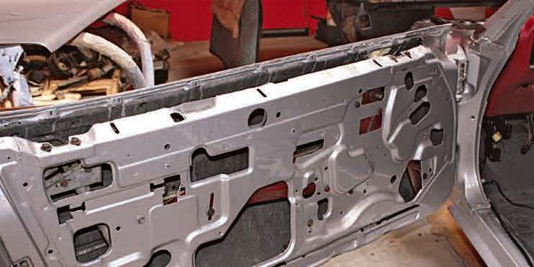Disassemble the doors while they are still on the car. The doors weigh more than 100 pounds each and any weight that can be removed from them is helpful in preventing injury and minimizing the potential for damaging the door.  Remove the door glass and window regulator from the door using a 1/4-inch drive socket and ratchet set. The door glass lifts out from the top. The glass may need to be tilted at a 45-degree angle from the back so the rollers clear the track.  The window regulator is bolted or riveted to the door shell. Most of the time the factory riveted in the power window regulators but bolted in the manual window regulators. If your door has rivets, simply drill the center of the rivet all the way through to release them.  Make sure the glass has already been removed. The outer glass weatherstrip located at the top of the door; Phillips-head screws hold it in.  Once you have removed these items, the door is still heavy but weighs less. Place a floor jack covered with a thick blanket or pad under the center of the door to help support it while you remove the hinge-to-hinge pillar 9/16-inch bolts. It is very helpful to have a friend hold the door as you do this. If no one is available, loosen the hinge bolts but do not fully remove them until you have the door well situated so it does not fall off when you remove the last bolt.