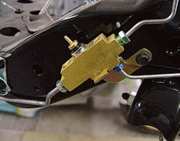 The distribution block is mounted on the frame rail below the master cylinder. This block was used on all cars, whether they had disc or drum brakes. (This is not a proportioning valve because it does not modulate pressure.) If there is a loss of pres¬sure in either the front or rear brak¬ing systems, it activates the brake warning light in the dash. To replace the distribution block, simply remove the lines, install them on a new block, and bolt the distribution block to the frame rail. If you replace the dis¬tribution block, you're opening the brake system, so you have to bleed it. Reproductions are available from Inline Tube. (Photo Courtesy Scott Tiemann)