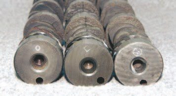 The camshaft identifier stamp was sometimes a shape instead of an alphanumeric character during the late 1970s. These three camshafts are 1977–1979 T/A 6.6 units. The valve events of each vary slightly. They are, from left to right: 1977 T/A 6.6 automatic transmission, 1977 T/A 6.6 manual transmission, and all 1978–1979 T/A 6.6.