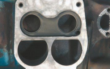 "The carburetor flange of the 4-barrel intake manifold was significantly modified in 1975 to accommodate the rerouted EGR system. It required a ""dish"" directly under the carburetor primaries, which gave the secondary openings a pronounced ""D"" shape. From looks alone, this manifold should significantly restrict airflow, but independent testing reveals otherwise. It is completely adequate for a strong-performing street engine."